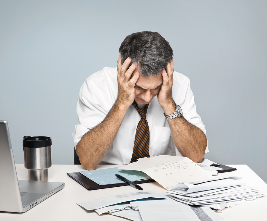 Man at desk in shirt and tie holding his head and worrying about money and the economy.
